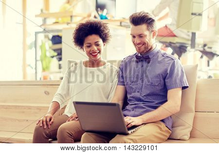 business, startup and people concept - happy creative team with laptop computer and folder in office