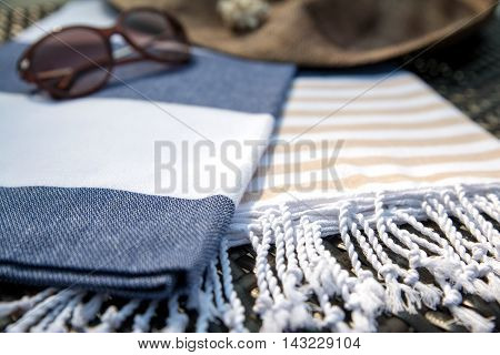 Concept of summer accessories close-up of white, blue and beige Turkish towel, sunglass and straw hat on rattan lounger with blue swimming pool as background.