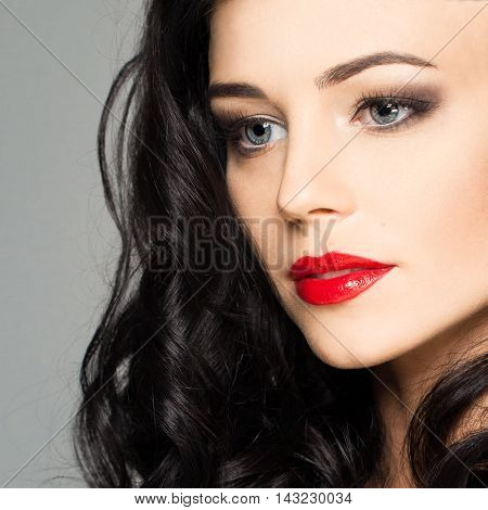 Cute female face with stage makeup smokey eyes and red lips