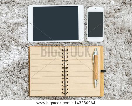 Closeup brown note book with line in page brown pen tablet and smart phone on gray fabric capet textured background in top view in work concept