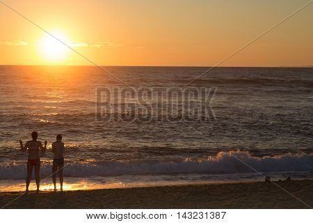 Colorful Sky With Going Down Sun, Young Pair At Beach