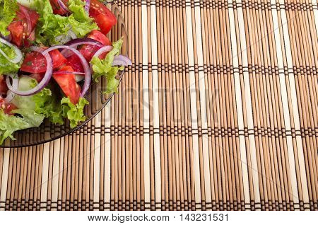 Background for food styling from a fragment of a transparent plate of fresh vegetarian salad of raw vegetables and bamboo mat