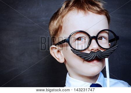 Funny little boy in father's glasses plays with false mustache. Childhood concept. Emotions.