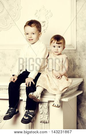 Beauiful little brother and his sister sitting together in  a room with classic vintage interior. Kid's fashion.