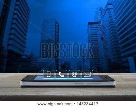Telephone mobile phone at and email buttons on modern smart phone screen on wooden table over city tower background Customer support concept