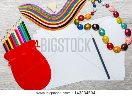 Pencils beads paper red bag on a wooden background