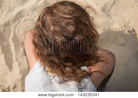 Good looking girl on beach laying on beach on stomach.