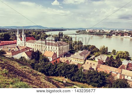 View from Esztergom basilica. Saint Ignatius church and Maria Valeria bridge Hungary. Travel destination. Red photo filter. Urban scene. Religious architecture. Danube river.