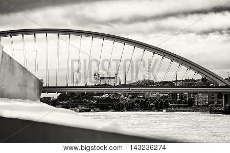 Bratislava castle behind modern Apollo bridge. Cruise on the Danube river. Black and white photo. Ship transportation. Architectural theme. Travel destination.