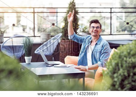 Hey waiter. Cheerful delighted smiling man sitting at the table and holding hand up while resting in the cafe