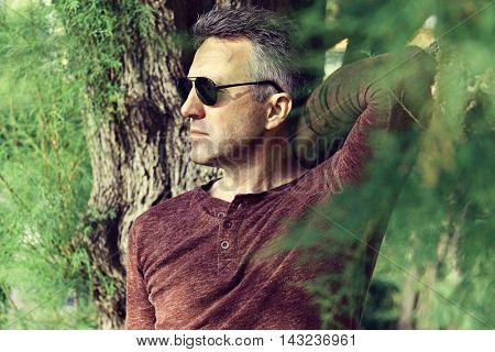 Outdoor portrait of handsome mid adult man posing in park. Male portrait, image toned and noise added
