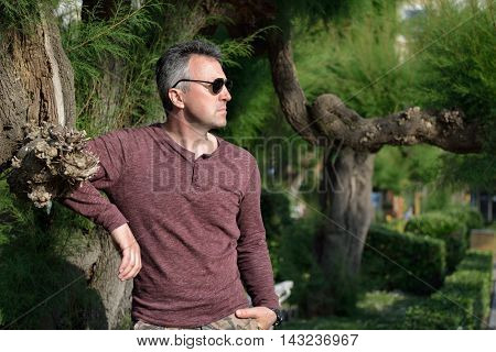 Outdoor portrait of handsome mid adult man posing in park. Male portrait, image toned.