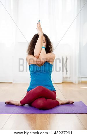Portrait of young woman sitting in yoga pose mix gomukhasana and garudasana in gym, vertical image