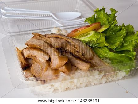 Roasted pork and rice in a plastic box