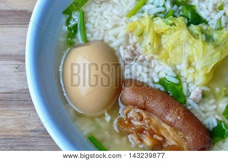 rice porridge topping brown egg and pork leg in bowl