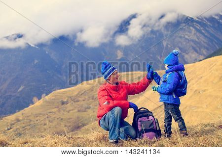 happy father and little son hiking in scenic mountains
