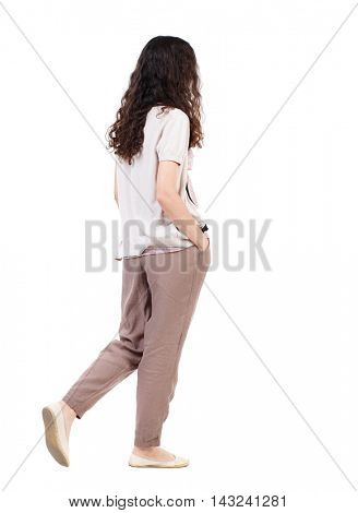 back view of walking  curly woman.  backside view of person.  Rear view people collection. Isolated over white background. Long-haired curly girl goes to the side with his hands in his pockets.