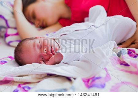 Little beautiful baby sleeping in bed with her young mother.