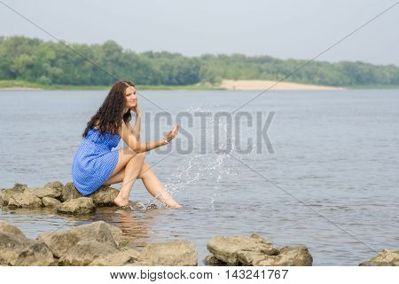 Happy Young Girl Sitting On The Bank Of The River Enjoying Condition Comes Summer
