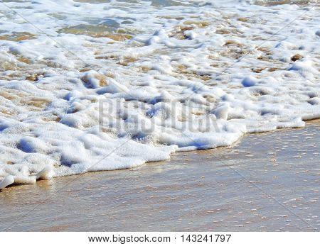 Sea surf on the beach, rolling waves background.