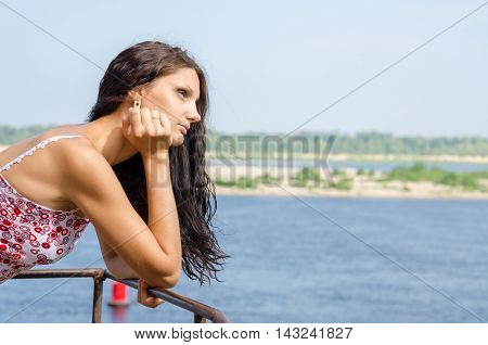 Young Brunette Girl Looking Thoughtfully Into The Distance On The Background Of The River