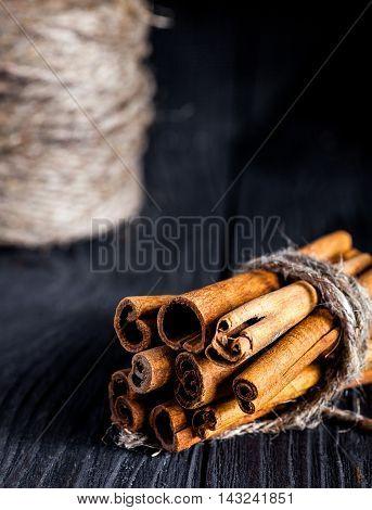 Cinnamon sticks tied with culinary thread on black wood board