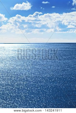 Blue, sparkling seascape with sun and fluffy clouds. Sea scene with copy space.