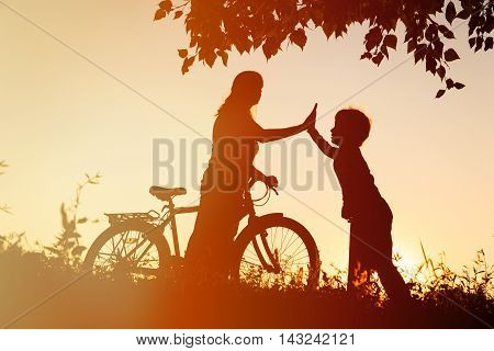 silhouette of happy mother and son riding bike and scooter at sunset