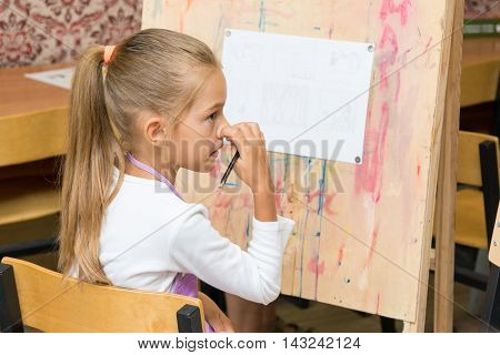 Girl Scratching Nose Listening To The Teacher Carefully At Drawing Lesson