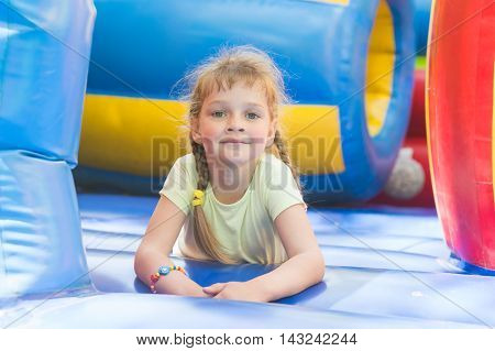 Disheveled Five Year Old Girl Is Playing On A Big Inflatable Trampoline