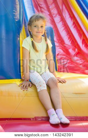 Five-year Girl Sitting On A Big Inflatable Trampoline