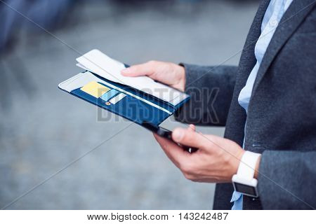 Modern way of life. Close up of valet in hands of pleasant businessman man holding it and using cell phone