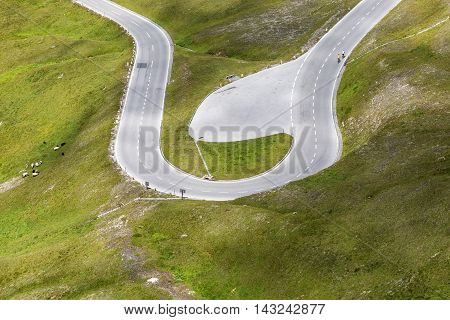 Cyclists ride uphill mountain road in the Alps. View from above. Road cycling