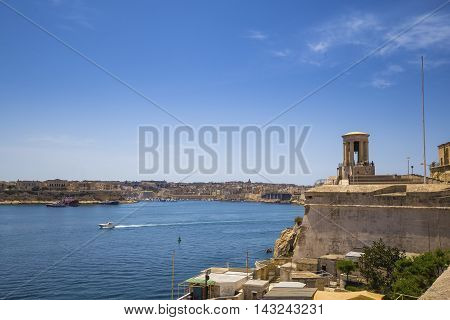 Malta - Siege Bell War Memorial and The Grand Harbour of Malta with clear blue sky
