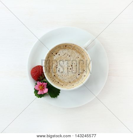 frothy coffee with decoration of fruit flower and leaf strawberries on a light wooden background top view / cappuccino garnished with strawberries