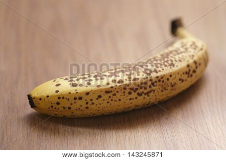 one banana with dots on wood table, shallow focus