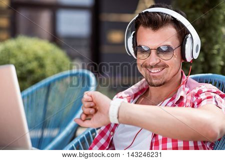 Full of emotions. Cheerful handsome smiling man using laptop and looking at his smart watch while listening to music