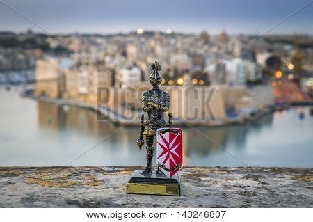 Maltese knight with the island of Birgu in the background at sunrise from Valletta, Malta