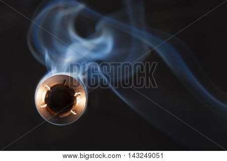 Copper plated bullet with a hollow point design and smoke behind