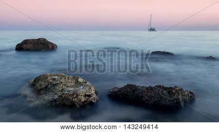 Lone boat on the horizon over a rocky shore in sunrise