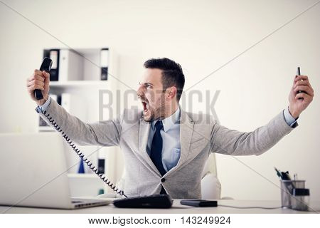 Businessman having stress in the office.Nervous young businessman screaming in his office.Having a headache after working really hard.
