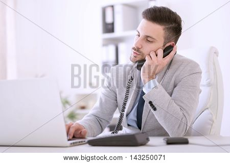 Businessman using laptop while talking on phone in the office