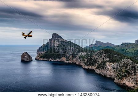 Firefighter plane flying over a beautiful seaside cliffs scenery at Cap de Formentor