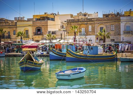 Malta - Traditional colorful Luzzu fishing boats at Marsaxlokk on a sunny summer day with blue sky and green sea