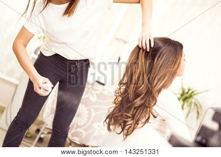 Hairdresser spraying his customer's hair.Young woman sitting while the hairdresser is styling her hair.