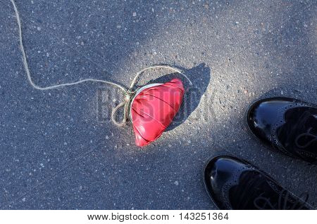 background with red purse and a thick rope tied to it is on the road in front of passers-top view / godsend a trick