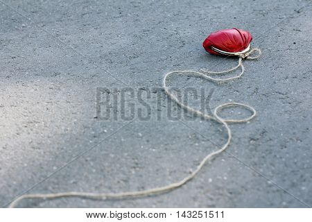 red purse with a rope tied to it is on asphalt road / tempting business a proposal