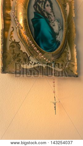 Hung on a painting an old rosary with crucifix on a light backgroundcopy space.used split toning for vintage/old style.