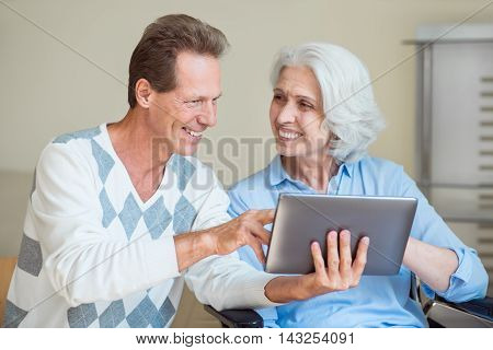 Always connected. Cheerful senior woman in wheelchair with her son holding digital tablet