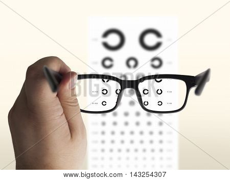 Eyeglasses in hand for eyesight. On the background of a chart test for eyes of Landolt C isolated